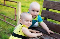 Małej dziewczynki i chłopiec wspinaczka na ławce zdjęcia stock