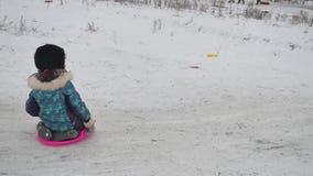 Małej dziewczynki jazda na śniegu ślizga się tocznego puszek wzgórza w zima czasu zimy wakacjach, Obraz Stock