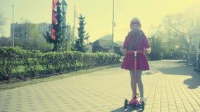 Małej dziewczynki jazda na hulajnoga zdjęcie wideo