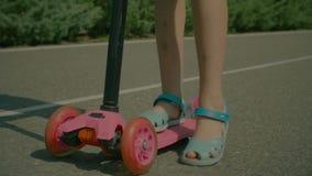 Małej dziewczynki jazdy pchnięcia hulajnoga park publicznie zbiory wideo