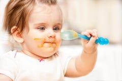 Małej dziewczynki karmienie od łyżki na błękitnym krześle Zdjęcia Royalty Free