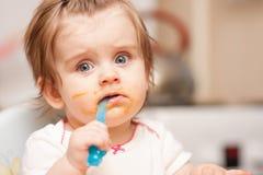 Małej dziewczynki karmienie od łyżki na błękitnym krześle Zdjęcie Royalty Free