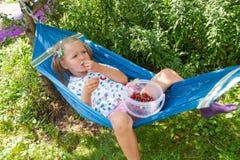 Małej dziewczynki lying on the beach na hammockand łasowania jagodach Zdjęcia Stock