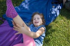 Małej dziewczynki lying on the beach w parkowej przyglądającej macanie nodze Obrazy Royalty Free
