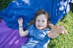 Małej dziewczynki lying on the beach w parkowy patrzeć próbujący dotykać ciebie Zdjęcie Stock