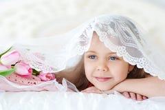 Małej dziewczynki lying on the beach z różowymi tulipanami Fotografia Stock