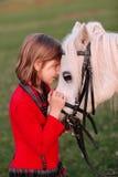 Małej dziewczynki Mały biały koń patrzeje each inny zdjęcia royalty free