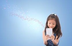 Małej dziewczynki mienie i patrzeć mądrze telefon z skutka płatka śniegu graficznym przepływem out od mądrze telefonu odizolowywa Zdjęcia Stock