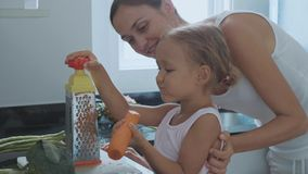 Małej dziewczynki nacierania marchewka na grater, kawałki i je je przy domową kuchnią zbiory