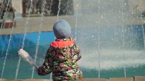 Małej dziewczynki obsiadanie blisko fontanny w parku zdjęcie wideo
