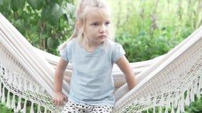 Małej dziewczynki obsiadanie na hamaku w lecie na gospodarstwie rolnym zbiory wideo