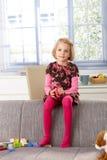 Małej dziewczynki obsiadanie na kanapa odpoczynku ono uśmiecha się obraz royalty free