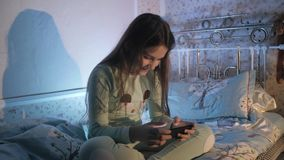 Małej dziewczynki obsiadanie na mieniu i łóżku smartphone w ona ręki zbiory wideo