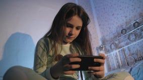 Małej dziewczynki obsiadanie na mieniu i łóżku smartphone w ona ręki zbiory