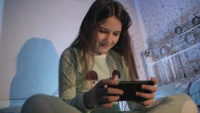 Małej dziewczynki obsiadanie na mieniu i łóżku smartphone w ona ręki zdjęcie wideo