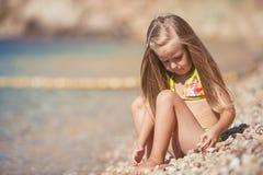 Małej dziewczynki obsiadanie na plaży blisko morza Zdjęcie Stock