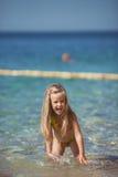 Małej dziewczynki obsiadanie na plaży blisko morza Zdjęcie Royalty Free