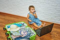 Małej dziewczynki obsiadanie na podłoga blisko laptopu i walizki przygotowywać dla wycieczki zdjęcie royalty free