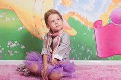 Małej dziewczynki obsiadanie na różowej podłoga Obraz Stock