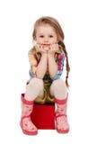 Małej dziewczynki obsiadanie na sześcianie, odizolowywającym obraz royalty free