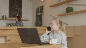 Małej dziewczynki obsiadanie przy kawiarnia stołowym używa laptopem zdjęcie wideo