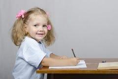Małej dziewczynki obsiadanie przy stołem i napisał w notatniku Fotografia Royalty Free