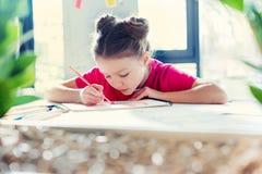 Małej dziewczynki obsiadanie przy stołem i rysunek z ołówkiem zdjęcia stock