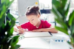 Małej dziewczynki obsiadanie przy stołem i rysunek z ołówkiem zdjęcie royalty free