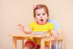 Małej dziewczynki obsiadanie przy stołem przed książką Zdjęcia Royalty Free