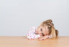Małej dziewczynki odpoczynkowa głowa na drewnianej powierzchni przy stołem Zdjęcie Royalty Free