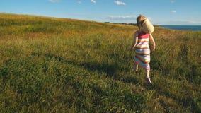 Małej dziewczynki odprowadzenie przy naturą i cieszyć się widokiem wybrzeże, pole piórkowa trawa i położenia słońce, zdjęcie wideo