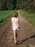 Małej dziewczynki odprowadzenie wzdłuż lato drogi w drewna Obrazy Stock