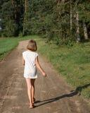 Małej dziewczynki odprowadzenie wzdłuż lato drogi w drewna Zdjęcie Royalty Free