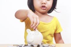 Małej dziewczynki oszczędzania pieniądze w prosiątko banku obrazy royalty free