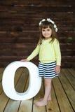 Małej dziewczynki pozycja blisko dużego listu O Obrazy Stock