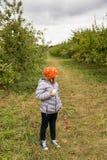 Małej dziewczynki pozycja w profilowym łasowania jabłku obraz stock