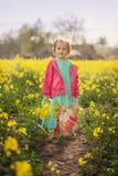 Małej dziewczynki pozycja w wiosna koloru żółtego łące Dziecka zrywania lata kwiaty Dzieci w kraju obraz stock