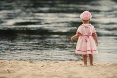 Małej dziewczynki pozycja z ona na plaży z powrotem fotografia stock