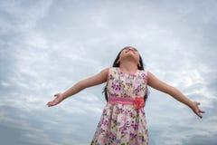 Małej dziewczynki pozycja z rękami szeroko rozpościerać tła niebo Zdjęcia Royalty Free