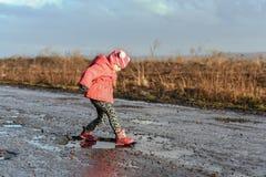 Małej dziewczynki przepustka kałuża, dziecka ` s zabawa, niezapomniani momenty, zabawa z ojcem, życie w wiosce, światło słoneczne Obrazy Stock