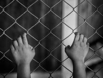Małej dziewczynki ręka trzyma dalej łańcuszkowego połączenia ogrodzenie dla wolności, istota ludzka obrazy royalty free