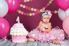Małej dziewczynki ` s urodzinowa dziewczyna mazał w tort Pierwszy tort Use pierwszy tort Roztrzaskanie tort Zdjęcia Stock