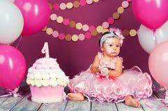 Małej dziewczynki ` s urodzinowa dziewczyna mazał w tort Pierwszy tort Use pierwszy tort Roztrzaskanie tort Fotografia Royalty Free