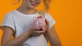 Małej dziewczynki uderzania prosiątka bank, osobiste oszczędności i budżet, planistyczna przyszłość zdjęcie wideo