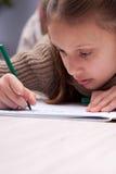 Małej dziewczynki writing koncentrujący na jej ćwiczenie książce Obrazy Royalty Free