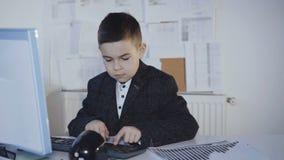 Małej przystojnej chłopiec ciężki działanie z komputerem w biurze 4K zbiory wideo