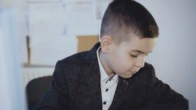 Małej przystojnej chłopiec ciężki działanie z komputerem w biurze 4K zdjęcie wideo