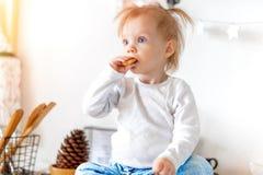 Mały śliczny berbeć dziewczyny łasowania owsa ciastko i obsiadanie na kuchennym stole obraz royalty free
