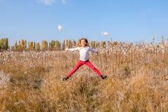 Mały śliczny caucasian biały dziewczyny doskakiwanie w polu z puszystym obraz stock
