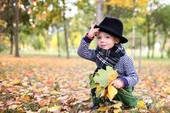 Mały śliczny dżentelmen w czarnym kapeluszu w jesień parku Zdjęcia Royalty Free